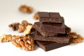 Chocolate blocks and walnuts on white — Stock Photo
