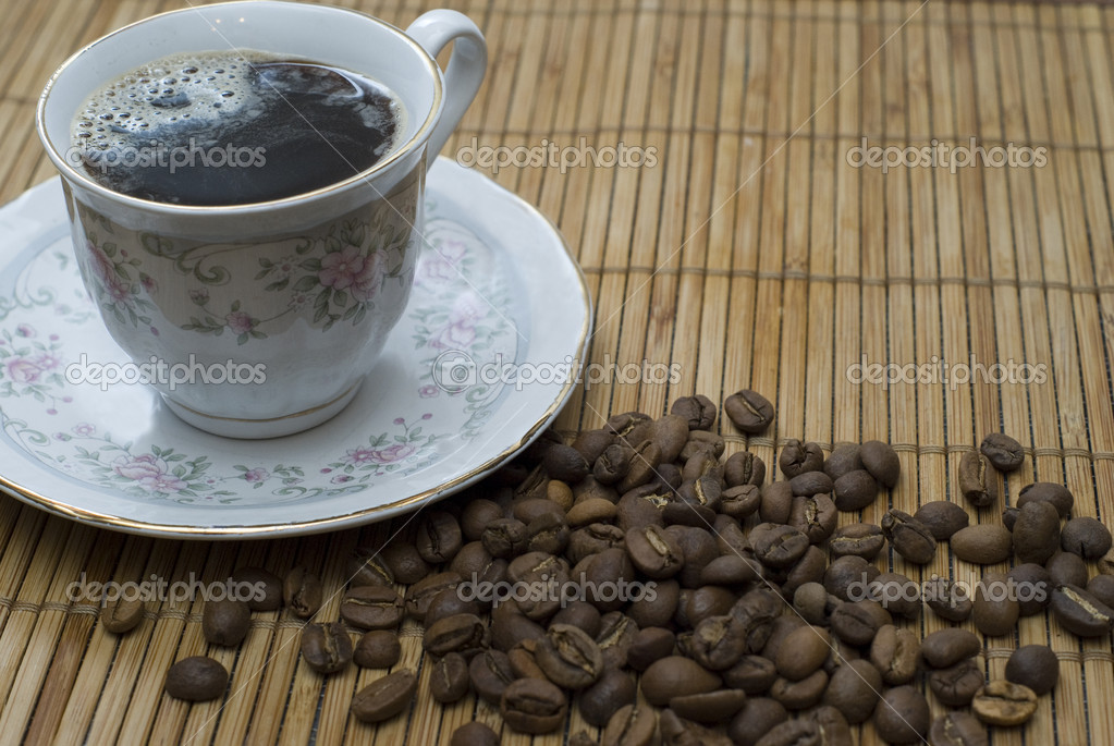 Flavorful cup of coffee and coffe beans on placemat  Stock Photo #2002621