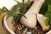 Mortar with fresh herbs and allspice — Stock Photo