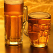 Beer mugs with froth over yellow — Stock Photo