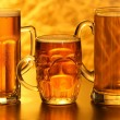 Stock Photo: Beer mugs with froth over yellow