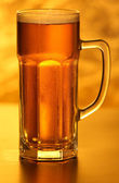 Mug of lager beer with bubbles on yellow — Stock Photo