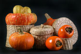 Wicker box with persimmon and pumpkins — Stock Photo