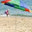 Striped umbrella on a sandy beach - Stock Photo