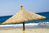 Straw parasol on the beach — Stock Photo