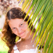 Joyful girl behind a palm branch — Stock Photo