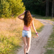 Girl walks on a footpath - Stock Photo