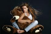 Jeune jolie femme avec gros ours en peluche — Photo