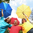 Foto Stock: Funny colorful friends with umbrellas