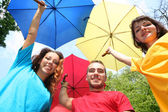 Funny colorful friends with umbrellas — Stock Photo