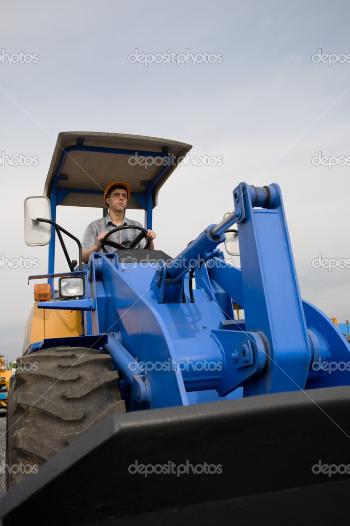 Construction worker driving a bulldozer on a building site  Stock Photo #1803247