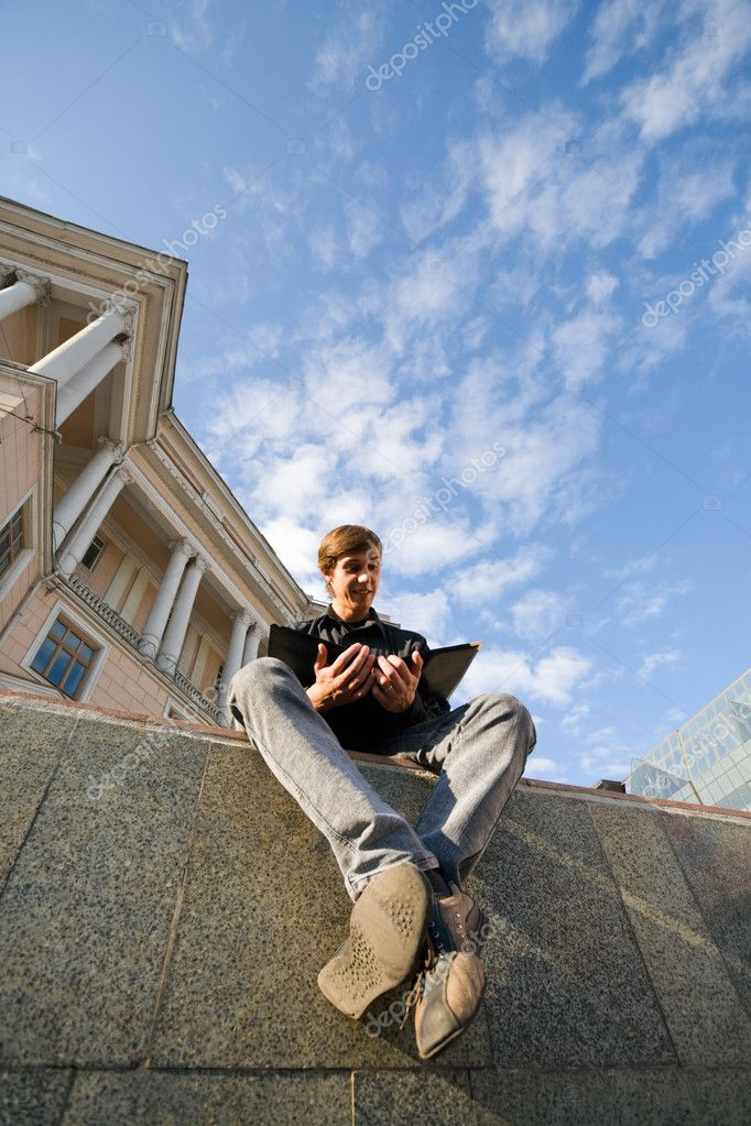 The young man (student) sits at a building of university and reads the book. — Stock Photo #2676547