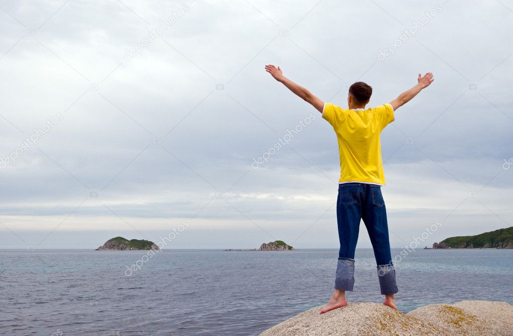 The man stands on rocks having stretched hands. Evening. Coast. — Stock Photo #2689754