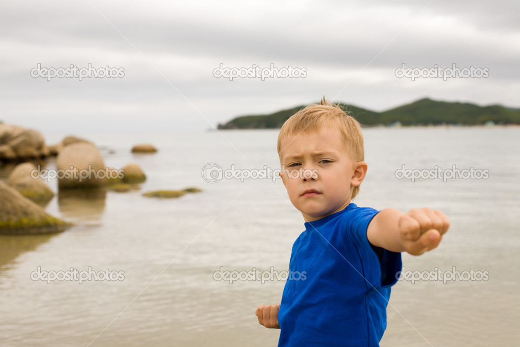 Karate boy in a fighting position on seacoast.Boy 5 years. — Stock Photo #2692607