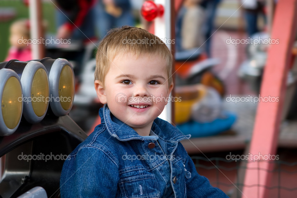 Cute toddler boy riding a car on a merry-go-round — Stock Photo #1804145