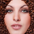 Woman's face with coffee beans — Stock Photo