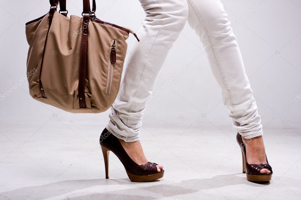 Legs of woman and bag at white background — Stockfoto #1823465