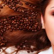 Woman's face with coffee beans — Stock Photo #2341858