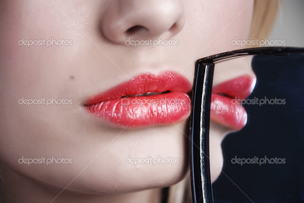 Scarlet lips are reflected in a little mirror which a girl holds in a hand — Stock Photo #2342353