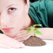 Young woman and green sprout — Stock Photo