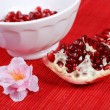Red seeds and white bowl - Stock Photo