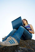 Woman with laptop and blue sky — Stock Photo