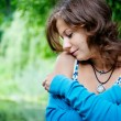 Romantic young woman relaxing outdoors - Stock Photo