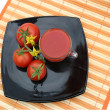 Black plate with red tomatoes — Stok fotoğraf