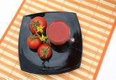 Black plate with red tomatoes — Stock Photo