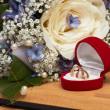 Stock Photo: Wedding details: bouquet and rings.