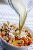 Pouring milk over muesli with dried frui — Stock Photo
