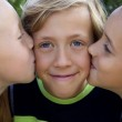 Cute blonde boy kissed by two girls — Stock Photo