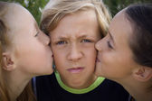 Young boy kissed by two girls — Stock Photo