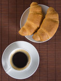 Cup of black coffee with croissants — Stock Photo