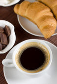Black coffee served with croissant — Stock Photo