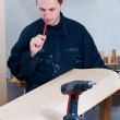 Carpenter with pencil in mouth holding part of the door — Stock Photo #1755538