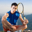 Young man take a break during training tennis on top of the rock — Stock Photo #2291425