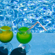 Royalty-Free Stock Photo: Glasses with cocktail on edge of pool