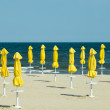 Deserted beach and beach umbrellas — Stock Photo