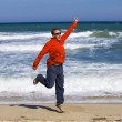 Man jumps  on sand on seashore - Stock Photo