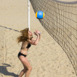 Woman plays in beach volleyball - Stock Photo