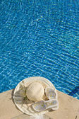 The straw hat lies on the brink of pool — Stock Photo