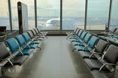 Empty armchairs at the airport and plane — Stock Photo