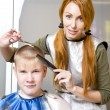 Stock Photo: Pretty woman hairdresser cuts client