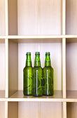 3 green glass bottles on a regiment — Stock Photo