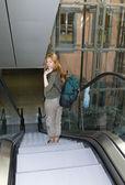 Frau mit rucksack auf der rolltreppe — Stockfoto