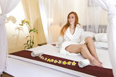 Young woman in house clothes on a bed — Stock Photo