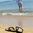 Beach slippers on sand and girl — Stock Photo #2195701