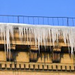 Huge icicles hang down from roof - Stock Photo