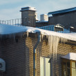 Huge icicles hang down from roof - Stockfoto